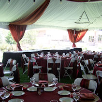 A tent set up with added ceiling swag and pole drapes