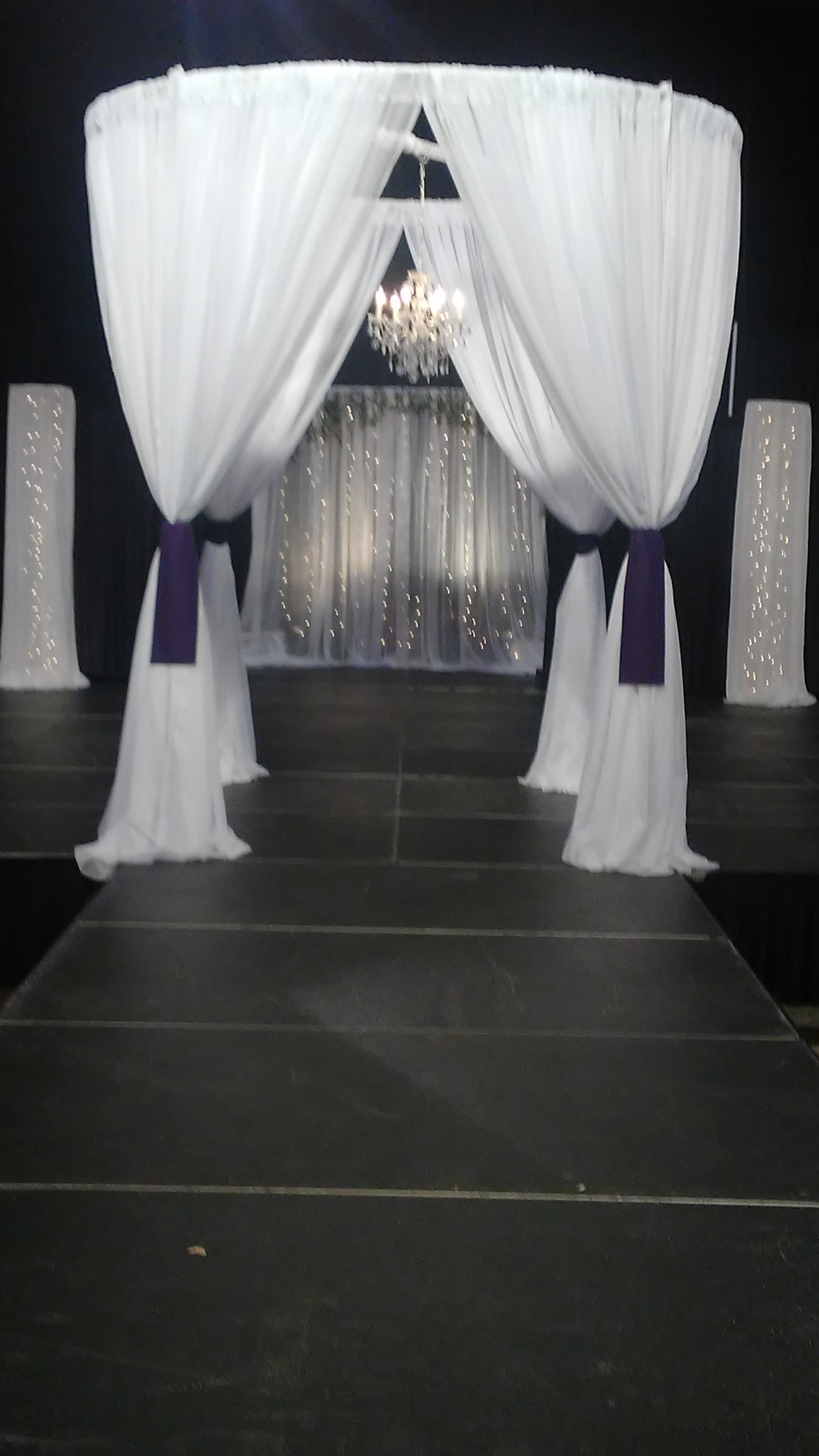 Back lit sparkle wall with round chuppah and light columns