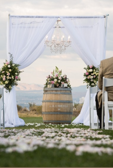White Fabric Alter or Chuppah adorned with flowers and wine barrels for a gorgeous look